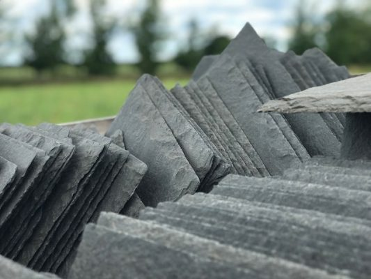 image showing reclaimed slates in a pallet with blurred countryside background, The Reclaimed Company