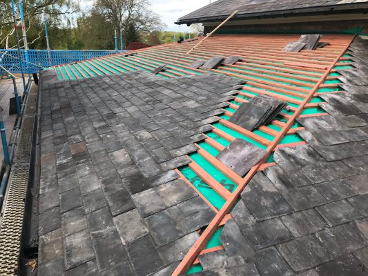 reclaimed building materials used to restore grade 2 listed property. Image shows reclaimed welsh slating in progress on a roof area.