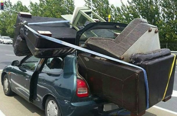 small car with furniture protruding from the boot and strapped to the roof, not architectural salvage.